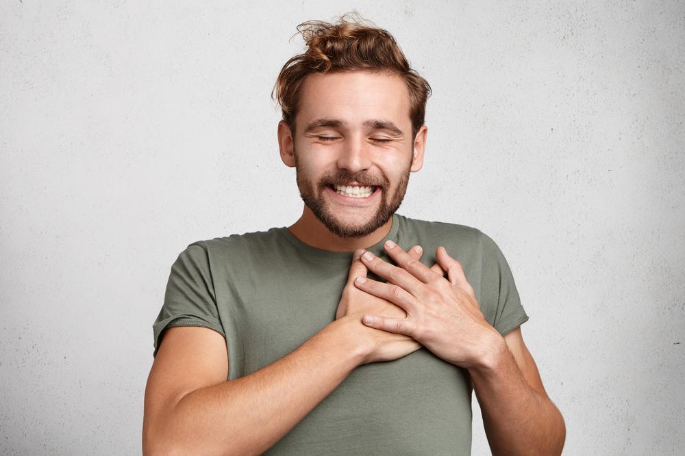 Herzlicher, glücklicher Hipster-Typ lächelt glücklich, schließt die Augen mit Freude, hält die Hände auf Herz, drückt angenehme Gefühle Mitgefühl und große Liebe aus.