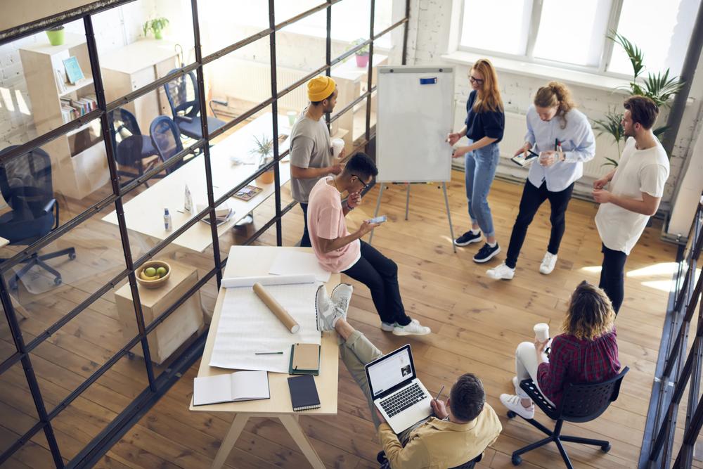 Top-Sicht der Diversitätsgruppe, die gemeinsam an einem Architekturprojekt im Büroinneren arbeitet, junge kreative GrafikdesignerInnen von Männern und Frauen, die beim Brainstorming mit moderner Technik zusammenarbeiten